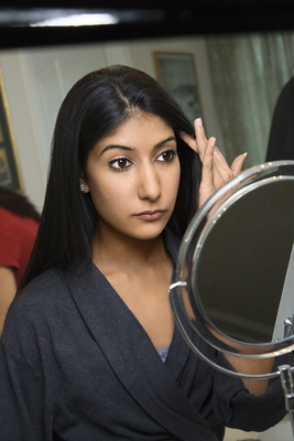Young woman looking in mirror.
